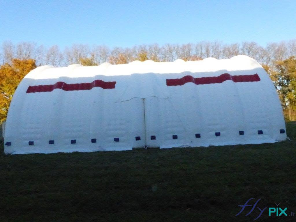 2 modules d'abris gonflables militaires en forme de tunnel et raccordés par des enveloppes en PVC, et haubanés.