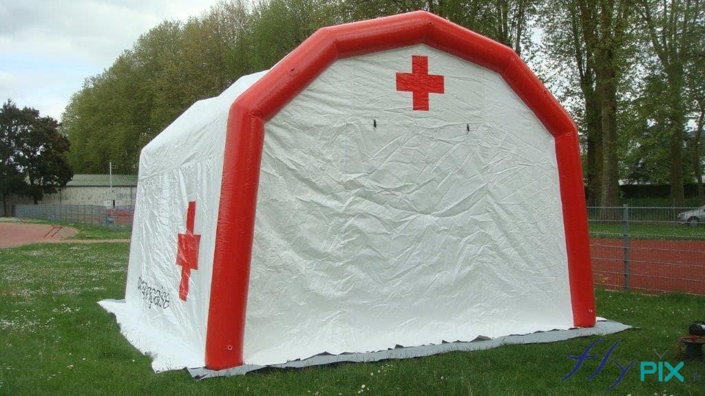 Tente PMA gonflable, face avant, avec l'entrée via une large porte pignon, et un marquage imprimé du logo de la croix rouge au dessus.