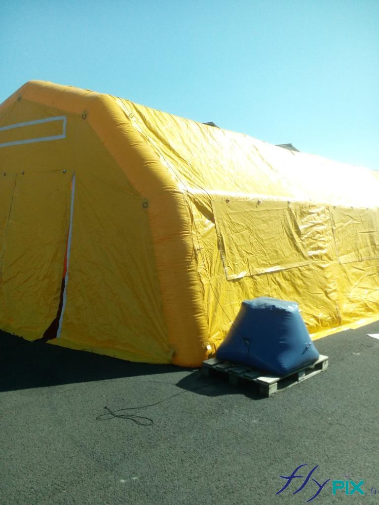 Porte d'accès principale de la tente médicale gonflable et sac de lestage à remplir de sable pour les haubans.