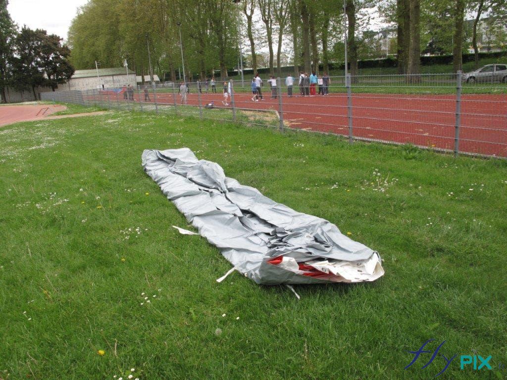 Tente gonflable dépliée au sol, prête à être gonflée avec une pompe électrique.