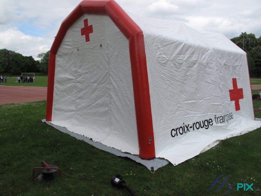 Un abri médical gonflable de couleur rouge et blanche, fabriqué pour la Croix Rouge Française.