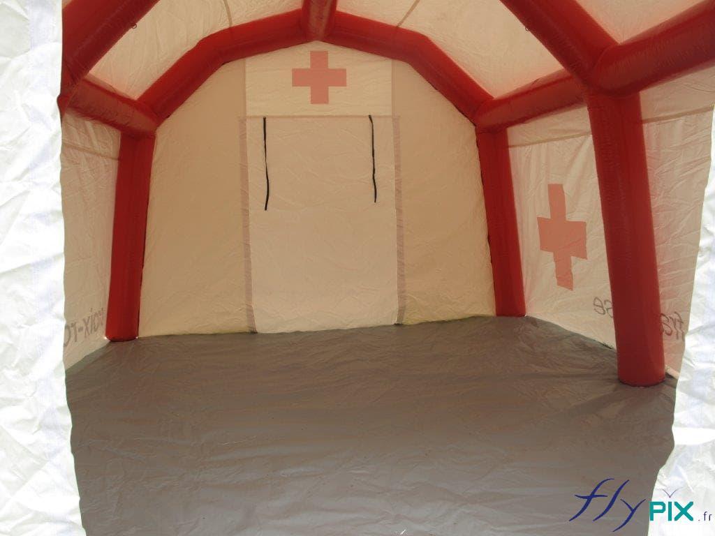 La tente médicale fermée a une bâche au sol, ici la porte est fermée