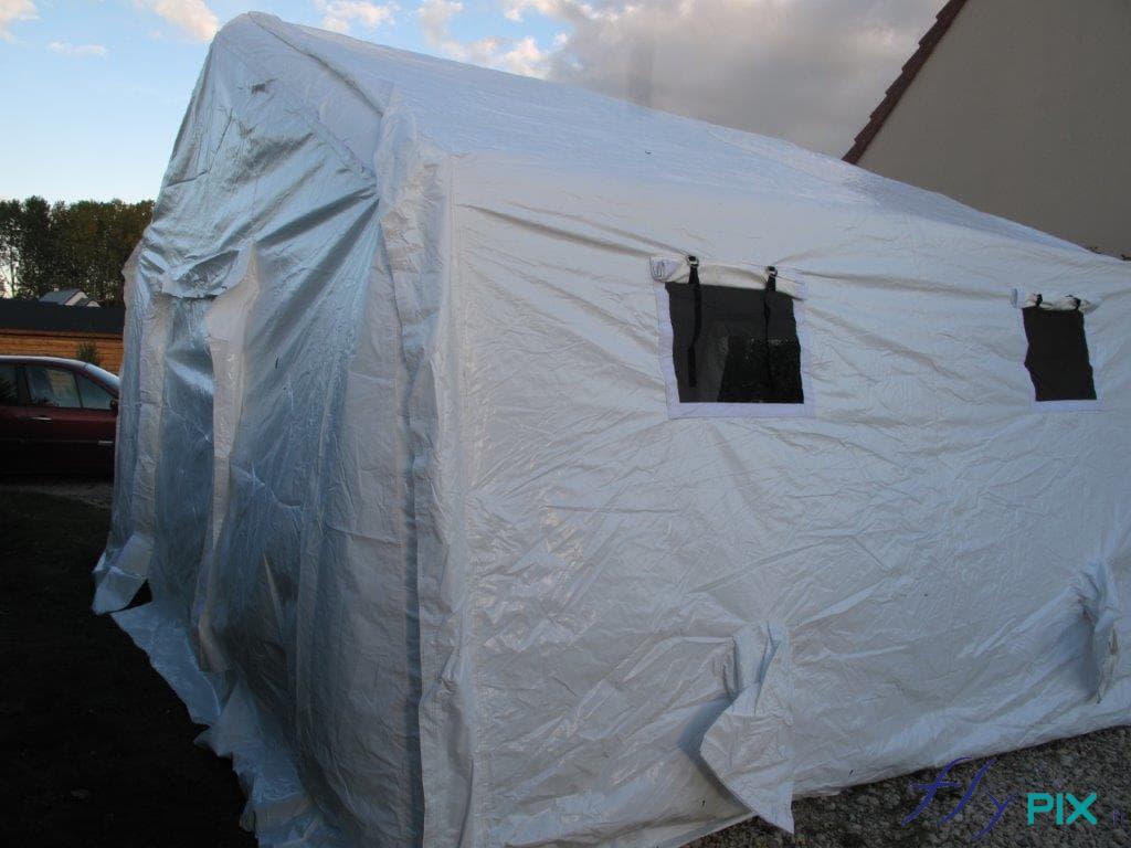 Tente médicale en forme de chapiteau, avec porte large pignon et fenêtre moustiquaire avec volets.