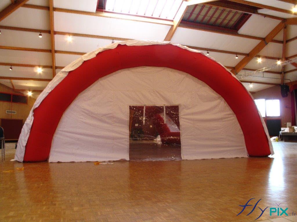 Une tente gonflable poste médical avancé, en forme de tunnel, et de grande taille, avec un porte large pignon transparente.