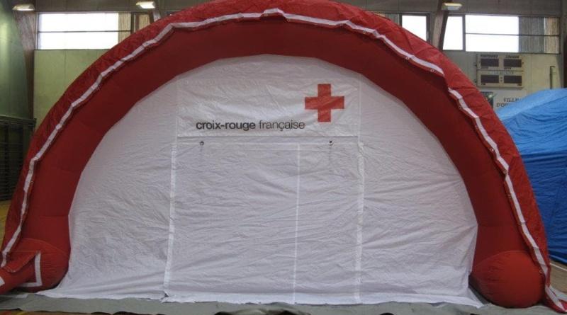 Une tente médicale gonflable en forme de demi-lune, avec le logo de la Croix Rouge Française et une porte large pigon.