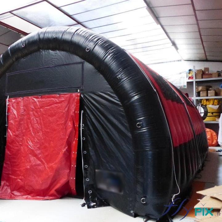 Une tente gonflable en forme de tunnel, en enveloppe PVC 0.6 mm et double peau capitonnée, de couleur noire avec des portes rouges.