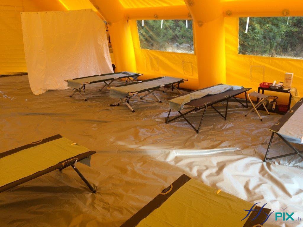 Lits picots installés à l'intérieur d'une tente PMA de grande taille.
