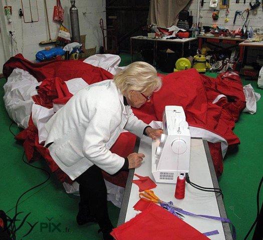 Une technicienne réalise une réparation sur une toile d'enveloppe de tente PMA