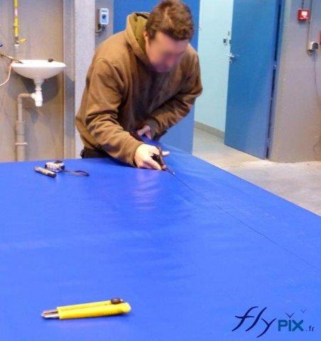 Un technicien est entrain de découper du PVC.