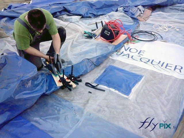 Technicien effectuant la réparation d'un mur d'une tente médicale de grande taille.
