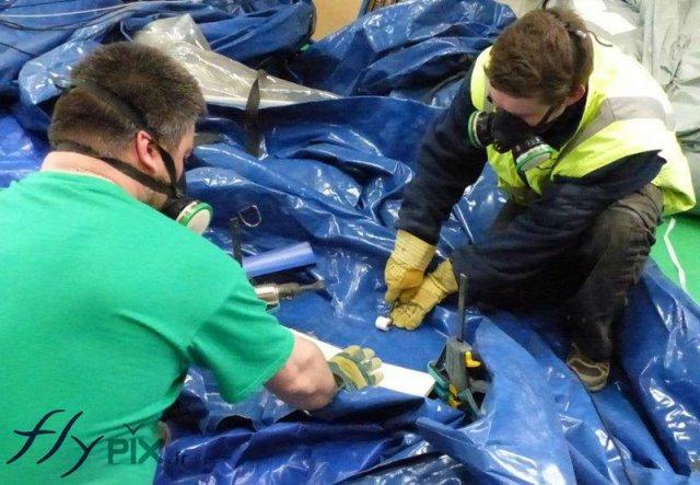 Deux techniciens sont entrain de réparer une tente médicale.