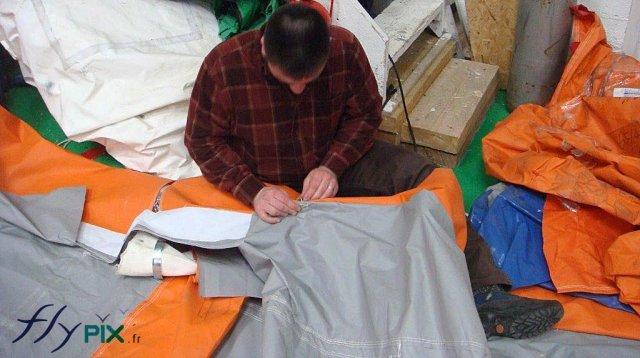 Un technicien est entrain de réparer l'enveloppe d'un mur d'une tente PMA
