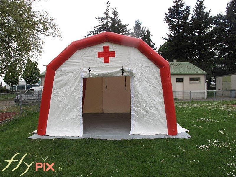 Un abri médical gonflable à pans coupés, fabriqué pour la Croix Rouge Française, avec une porte large pignon (ici ouverte), et une bâche au sol lavable en PVC.