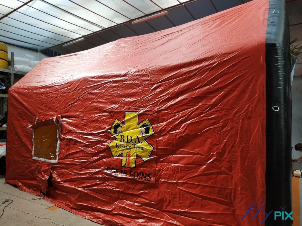 Une tente PMA, un poste médical avancé, avec sur les cotés latéraux une personnalisation par des banderoles imprimées amovibles fixées avec du velcro.