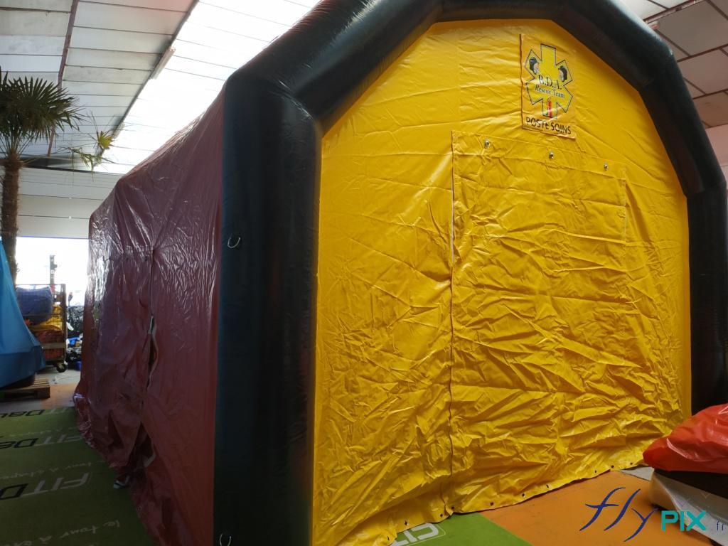 Une tente médicale gonflable de premiers secours, avec une porte large pignon, des marquages amovibles en banderoles velcro, et des boudins d'ossatures air captif étanche.