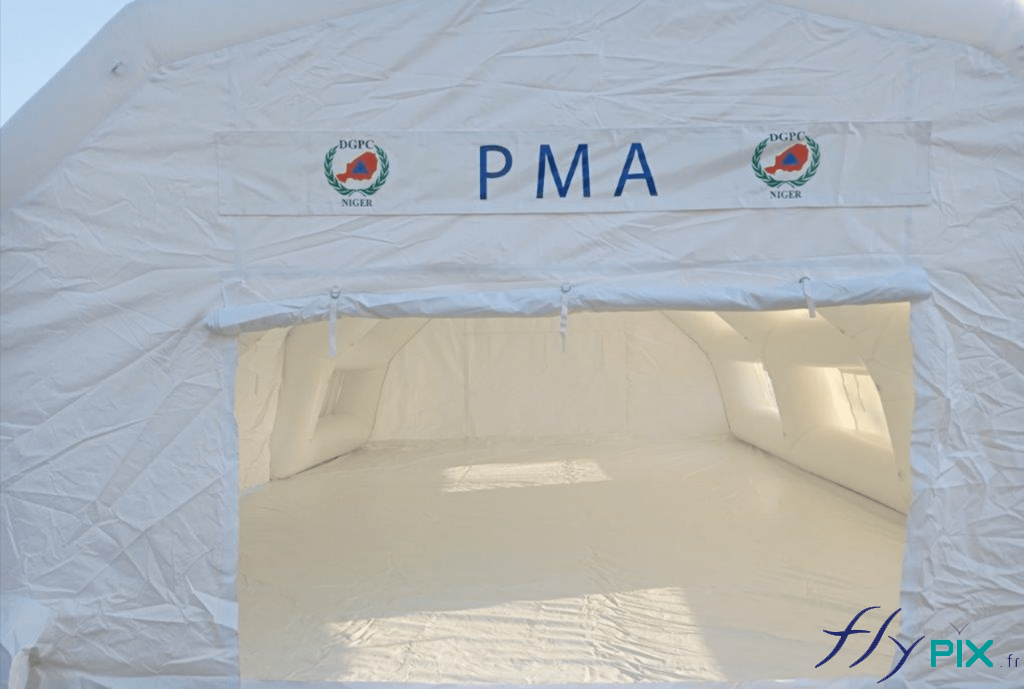 Porte large pignon de la tente PMA, avec au dessus une banderole imprimée fixée par du velcro.