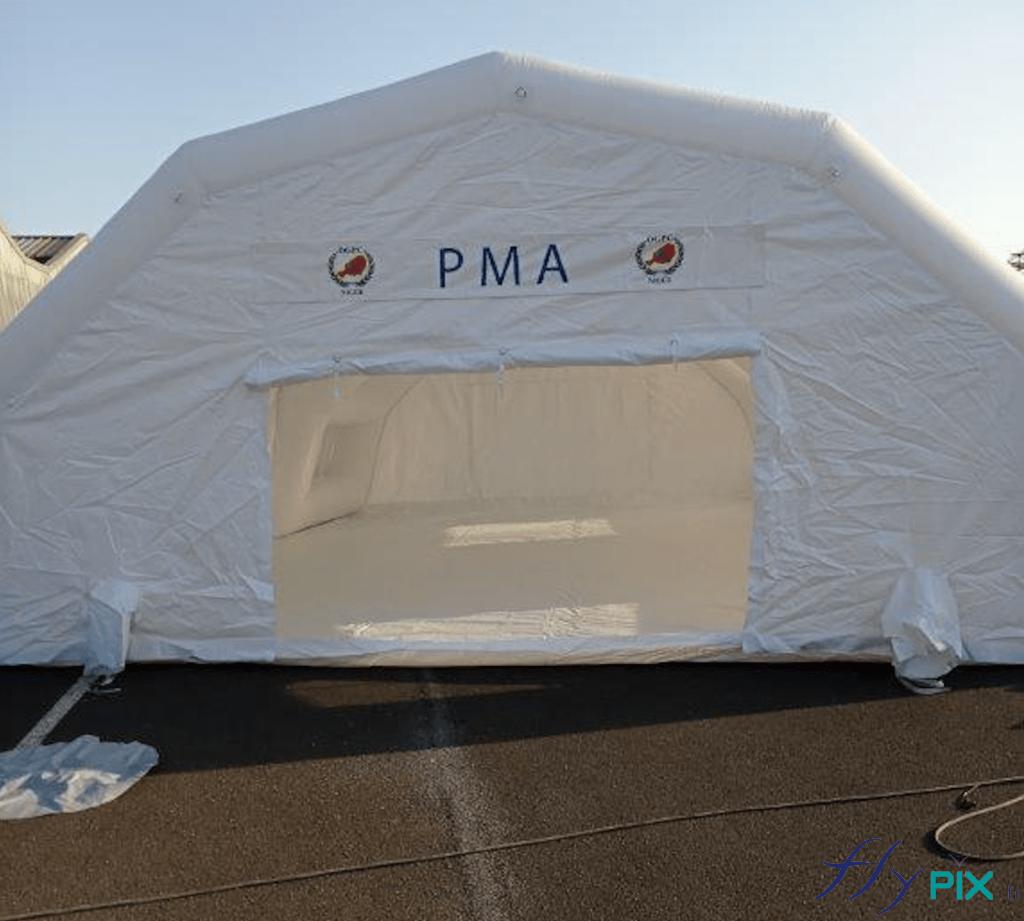 Vue extérieure de la tente PMA (Poste Médical Avancé), une structure gonflable air captif, gonflée avec une pompe électrique. Porte large pignon et banderole de marquage amovible fixée par velcro.