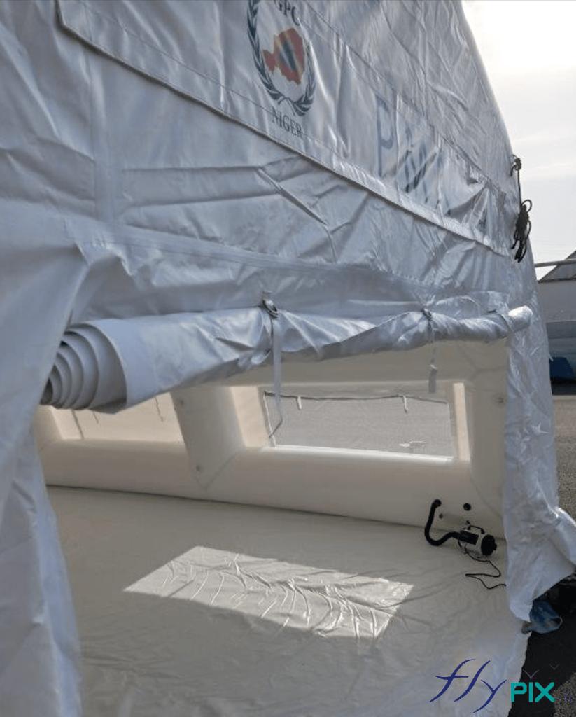 Une vue détaillée de la porte large pignon de la tente médicale gonflable air captif. On voit aussi la bâche au sol en PVC lavable.