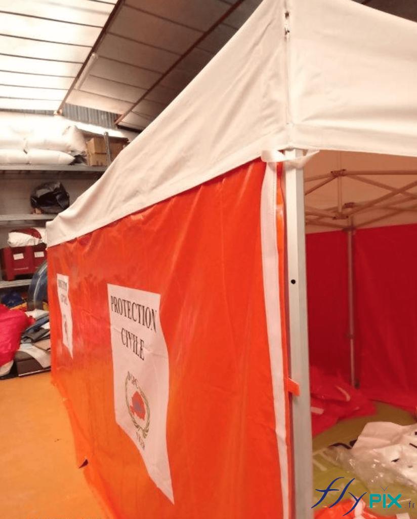 Vue détaillée des murs, avec marquages en impression numérique couleur, pour la tente médicale pliable.