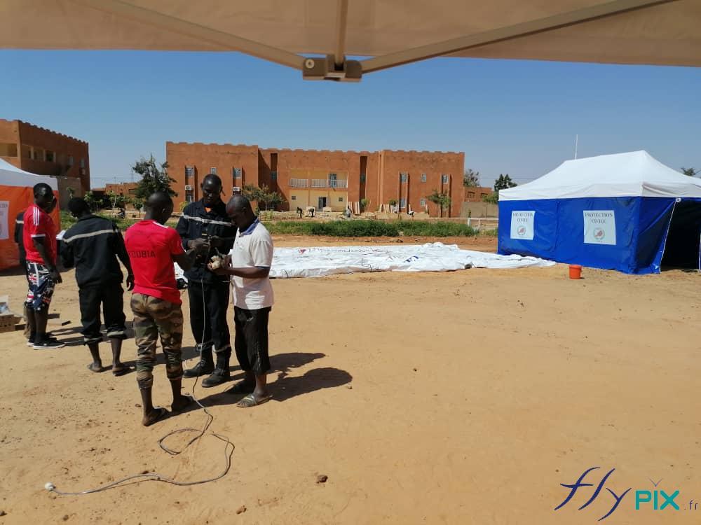 Des techniciens de la Protection Civile sont entrains de vérifier le matériel, pour la pose et l'installation de tentes médicales.