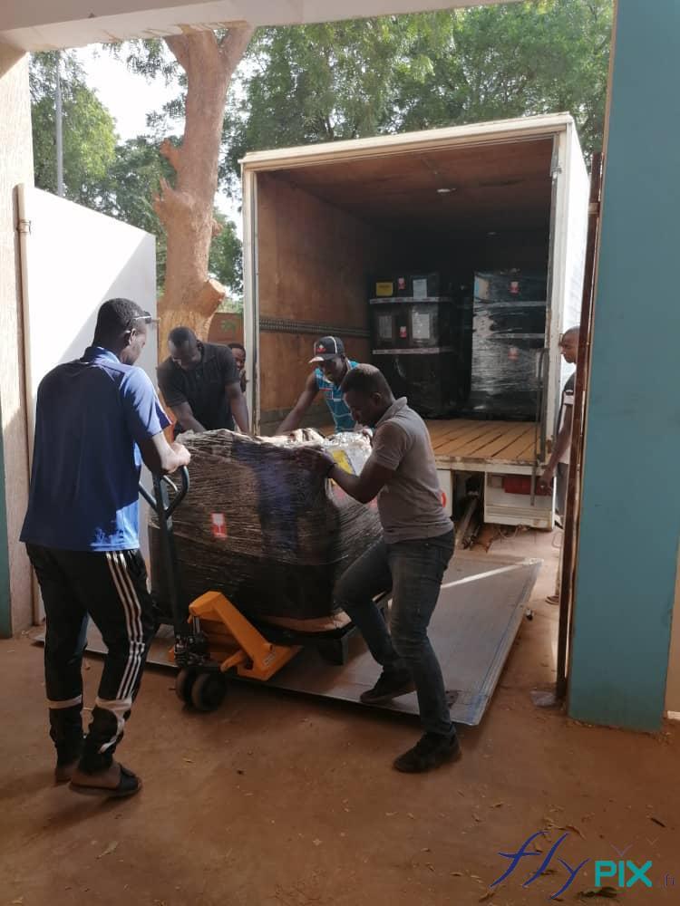 Des techniciens sont entrain de décharger un camion avec des palettes de tentes PMA pliables et gonflables.