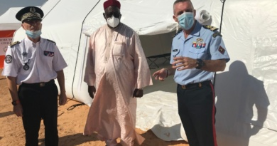Des officiers et des officiels posent devant une tente médicale gonflable, de grande dimension, air captif.