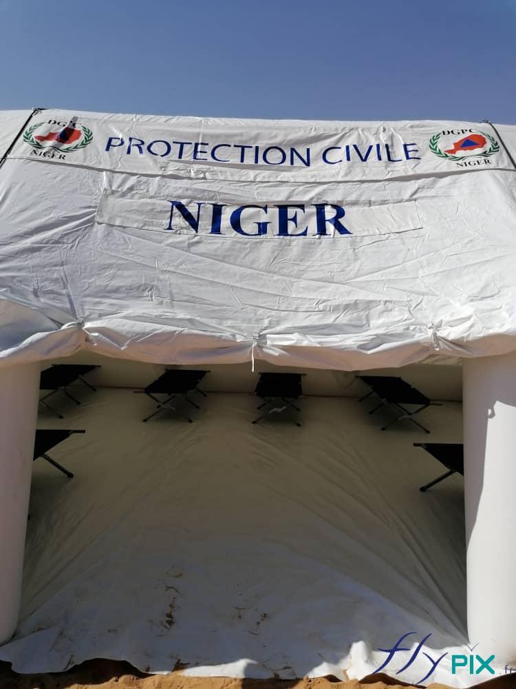 Au dessus de la porte de la tente PMA: des larges banderoles imprimées fixées par du velcro.