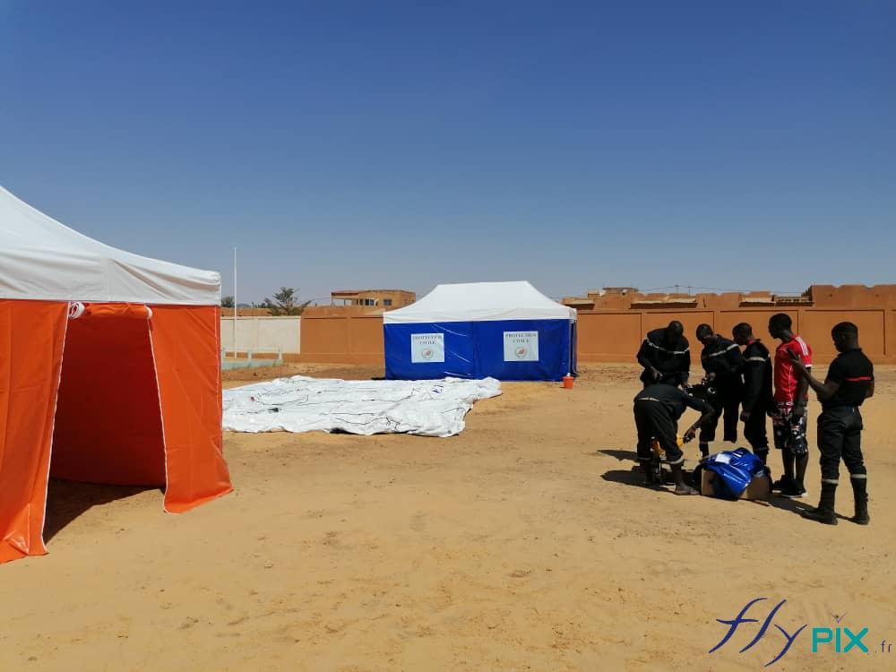 En Afrique, au Niger, La Protection Civile procède à la pose et au montage de tentes PMA pliable.